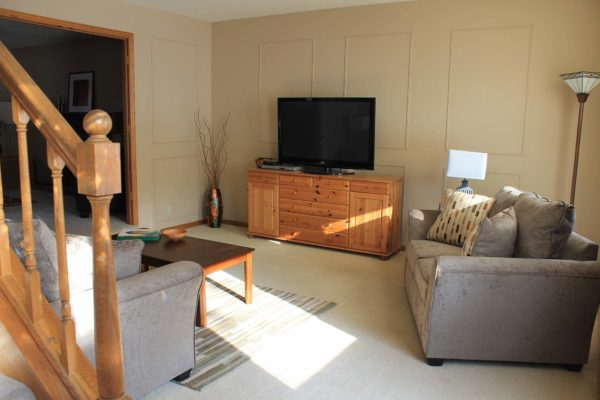 Forest Knoll family room after staging gray sofa with brown walls and pine tv stand