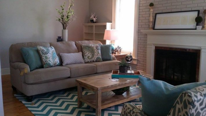 brown sofa with teal accents and fireplace staging